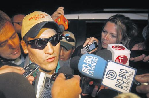 Rescued miner Carlos Mamani, from Bolivia, is surrounded by the press as he arrives at his home in Copiapo, Chile.