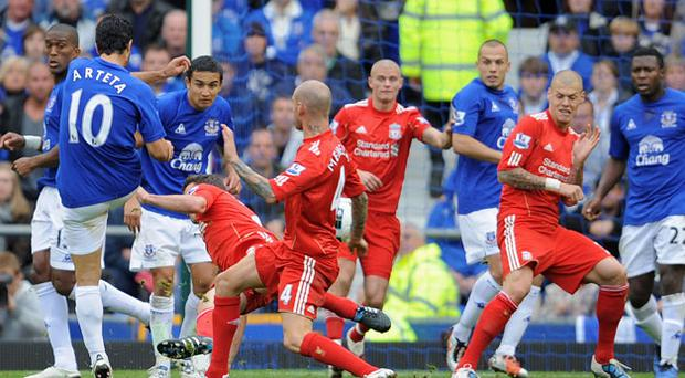 Liverpool are down and out as Mikel Arteta's shot flies past Pepe Reina to put Everton two up at Goodison Park yesterday. Photo: Getty Images