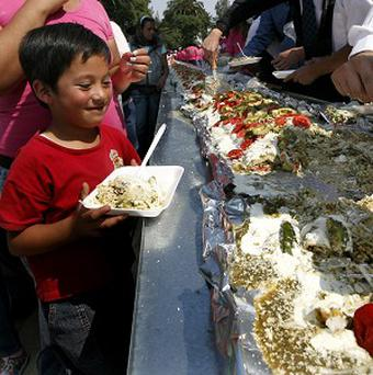 A boy waits to be served a portion of the world's largest enchilada (AP)