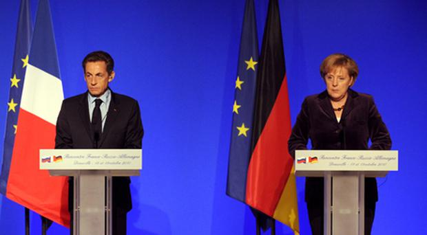 French President Nicolas Sarkozy and German Chancellor Angela Merkel give a press conference in Deauville, northwestern France, yesterday. Photo: Getty Images