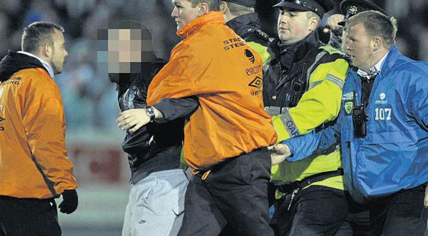 OCTOBER 19, 2010 - A 'fan' is led away by security staff and members of the Gardai at the end of the FAI Cup semi-final replay between St Patrick's Athletic and Shamrock Rovers at Richmond Park on Tuesday night.