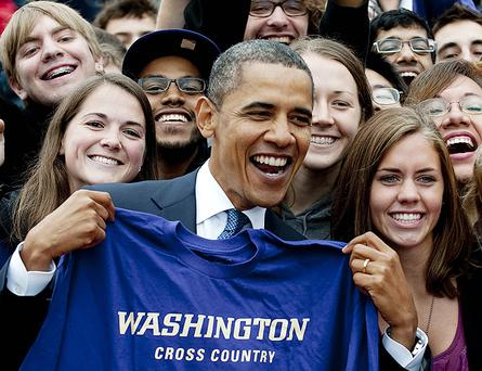 US President Barack Obama holds up a University of Washington Cross Country t-shirt during a rally for US Senator Patty Murray. Photo: Getty Images