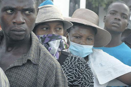 Relatives of people struck down with the disease wait outside a hospital for news.