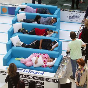 People sleep on settees during the first Siesta Championship in Madrid, Spain (AP)