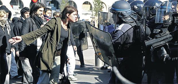 A protesting French student faces down riot police officers during a confrontation on the streets of Lyon last week