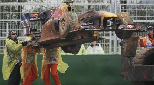 The car belonging to Red Bull driver Mark Webber is lifted from the track after he crashed during the Korean Grand Prix. Photo: AP