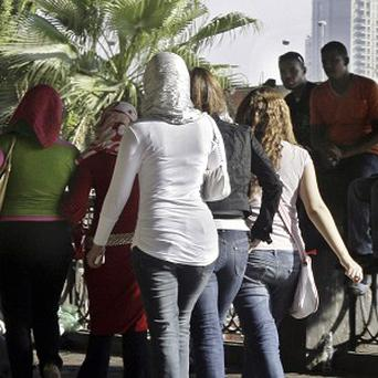 Egyptian boys watch passing girls at the Nile bank in Cairo, Egypt (AP)