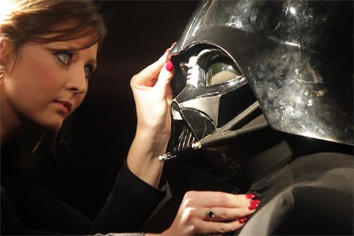 Christie's employee Caitlin Graham adjusts an original Darth Vader costume, which is to be auctioned off next month
