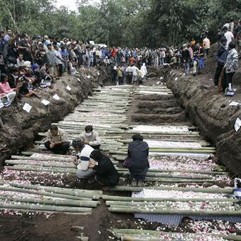 Relatives pray in the grave for the victims of Mount Merapi eruption during a mass burial in Indonesia (AP)