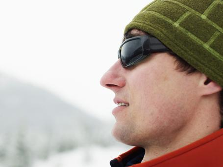 Man wearing hat and sunglasses looking at mountains, close-up, Joffre Pass, British Columbia, Canada