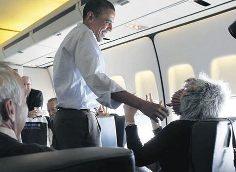 President Barack Obama jokes with a reporter wearing a Halloween mask on Air Force One yesterday. He was returning from Cleveland to Washington, where thousands gathered at the weekend for the Rally to Restore Sanity and/or Fear led by comedians Jon Stewart and Stephen Colbert (top left). REUTERS