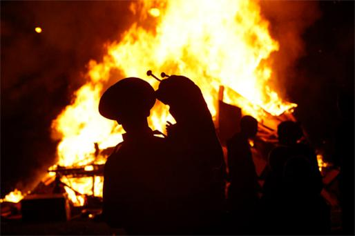 A father and his child in fancy dress watch a bonfire in Whitechurch Green in Ballyboden, Dublin, last night