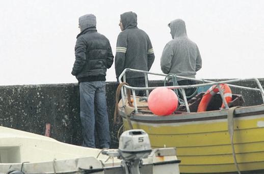 Local men look out from the pier at Glengad, Co Donegal, yesterday, where the body of Edward Doherty was recovered