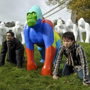 Tourists pose for pictures next to the life-size gorilla sculptures