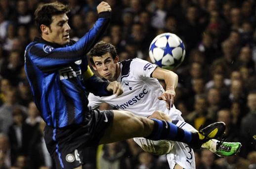 Gareth Bale gets in his shot despite the efforts of Inter Milan's Javier Zanetti at White Hart Lane last night. Photo: Reuters