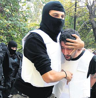 Anti-terrorism police escort a mail bomb suspect to a public prosecutor's office in Athens, Greece, yesterday