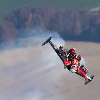 Swiss pilot Yves Rossy speeds through the air to perform a loop above Bercher, western Switzerland