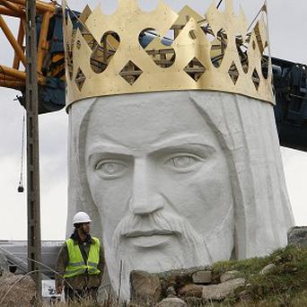 Workers prepare to lift the head and shoulders to top a giant concrete and metal statue of Jesus in Poland (AP)