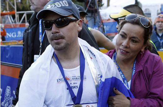 Chilean miner Edison Pena is embraced by his wife after he crossed the finish line of the New York City Marathon yesterday. He completed the gruelling race despite competing with an injury. Photo: Reuters