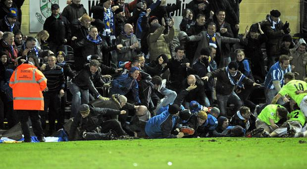 November 8 2010 - Monaghan United supporters fall as a wall collapses at the Carlisle Grounds on Monday night.