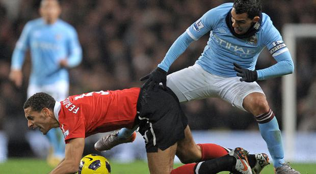 Carlos Tevez gets to grips with former team-mate Rio Ferdinand during last night's Manchester derby. Photo: Getty Images