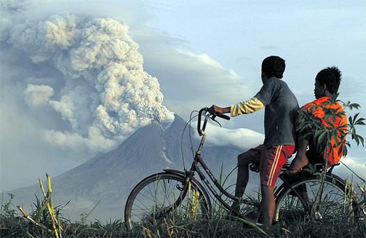 Boys look at the eruption of Mount Merapi volcano in Manisrenggo village, in the Klaten district of Indonesia's central Java province yesterday