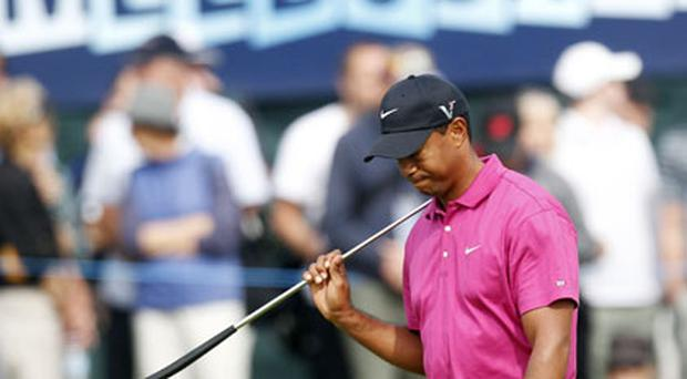 World number two and defending champion Tiger Woods leaves the 18th green during the first round of the Australian Masters at the Victoria Golf Club in Melbourne yesterday. Photo: Reuters
