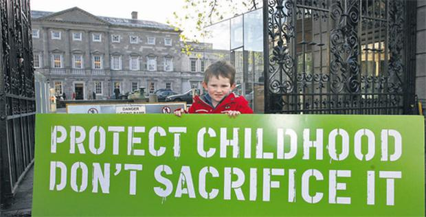 Three-year-old Jack with one of the Barnardos signs outside Leinster House at the launch of the charity's 'Dreading December 2010' report yesterday