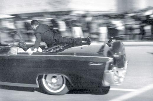 Clint Hill leaps on to the limousine carrying the mortally wounded President John F Kennedy as it races to hospital seconds after he was shot on November 22, 1963, in Dallas, Texas.