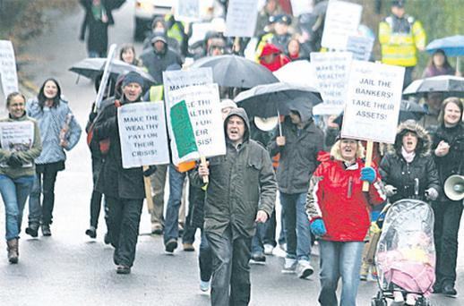 Demonstrators in Greystones, Co Wicklow, yesterday, marching on the home of disgraced banker Sean FitzPatrick