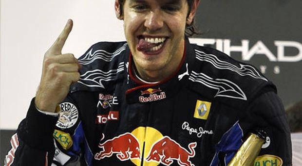 Red Bull's Sebastian Vettel celebrates on the podium after winning yesterday's Abu Dhabi Grand Prix and with it becoming F1's youngest World Champion. Photo: Reuters