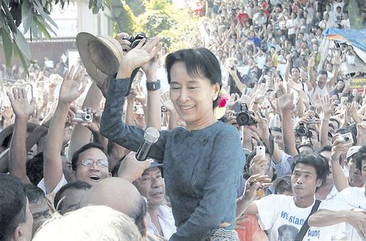 Burmese democracy leader Aung San Suu Kyi waves to supporters outside the headquarters of her National League for Democracy party in Rangoon yesterday.