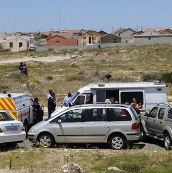 Police examine the car (centre) in which the body of Anni Dewani was found