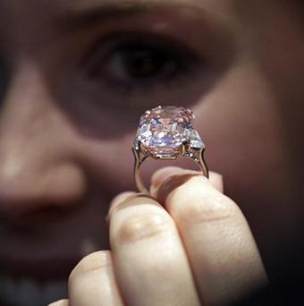 An employee of Sotheby's auction house holds a 24.78 carat fancy intense pink diamond mounted as a ring (AP)