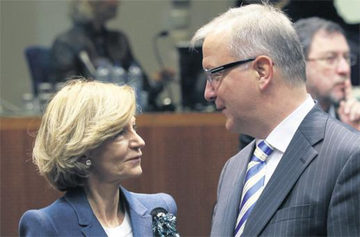 Spain's Economy Minister Elena Salgado talks to European Economic and Monetary Affairs Commissioner Olli Rehn at the start of an European Union finance ministers meeting in Brussels yesterday. Brussels is determined to prevent the debt contagion reaching Portugal's neighbour