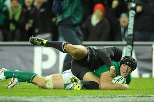 Stephen Ferris, Ireland , goes over to score his side's first try despite the efforts of Mils Muliaina, New Zealand. Photo: Sportsfile