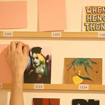 A member of staff takes down an artwork in the Secret Postcard Sale, at the Royal College of Art, in Kensington, central London