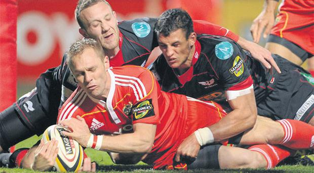 Paul Warwick goes over for Munster's first try despite the best efforts of Morgan Stoddart, left, and Aaron Shingler at Musgrave Park. BRENDAN MORAN/SPORTSFILE