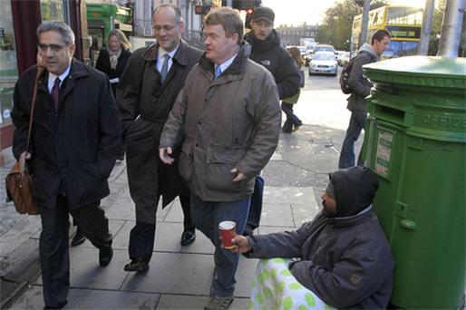 Ajai Chopra, far left, deputy director of the European Department of the IMF, walking past a beggar on his way to the Central Bank last week
