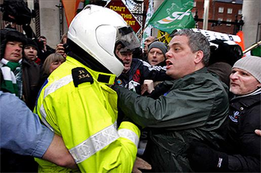 Sinn Fein TD Aengus O Snodaigh argues with a garda after dozens of party members broke through the gates of Government Buildings yesterday. Photo: Steve Humphreys