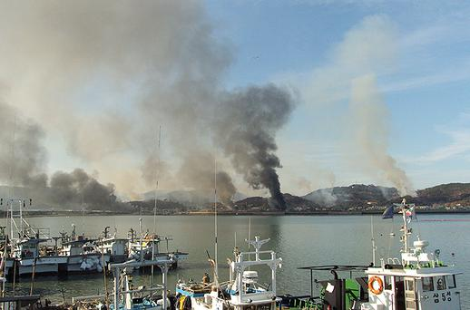 In this image provided by a local resident, Smoke rises from South Korea's Yeonpyeong island near the border against North Korea. Dozens of artillery shells fired by North Korea hit the South Korean Island of Yeonpyeong reportedly causing injuries and prompting return fire from South Korean forces