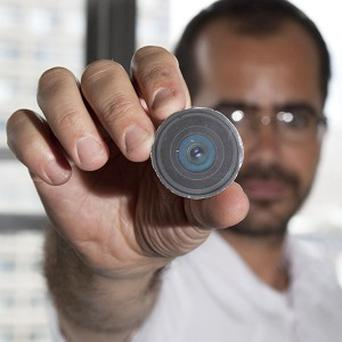 Arts professor Wafaa Bilal holding the prototype of a digital camera that he had implanted in the back of his head, in New York (AP)