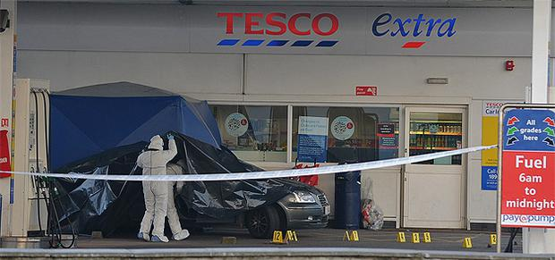 Garda forensic investigators on the forecourt of the Tesco petrol station at Clearwater in Finglas yesterday following the double murder of cousins Glen Murphy and Mark Noonan. Photo: Damien Eagers