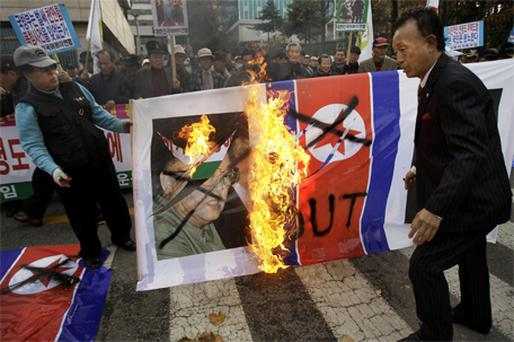 Protesters burn a portrait of North Korea's leader Kim Jong Il and his nation's flag in front of the defence ministry yesterday in Seoul, South Korea, as tensions rose between both parts of the Korean peninsula