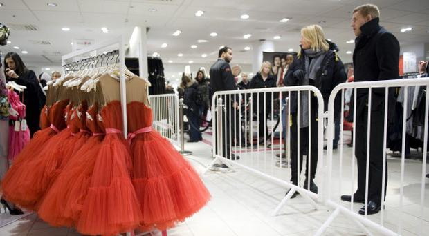 People stands outside a security barrier and look at dresses in a H&M store on November 23, 2010 in Stockholm, after the launch of a line by Lanvin's Israeli designer Alber Elbaz in 200 H&M stores worldwide, the latest of a string of tie-ups between the Swedish retailer and top fashion designers. For the operation Elbaz designed cocktail dresses with rose-patterning or yellow frills and sharp-tailored party frock numbers, with a democratic price tag of 99 to 149 euros (149-199 dollars), as well as blouses for 19.90 euros. AFP PHOTO / JONATHAN NACKSTRAND (Photo credit should read JONATHAN NACKSTRAND/AFP/Getty Images)