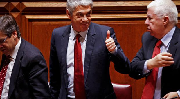 Portuguese Prime Minister Jose Socrates, centre, gives a thumbs up next to Finance Minister Fernando Teixeira dos Santos, right, after the final approval of his government's 2011 state Budget on Friday. Photo: AP