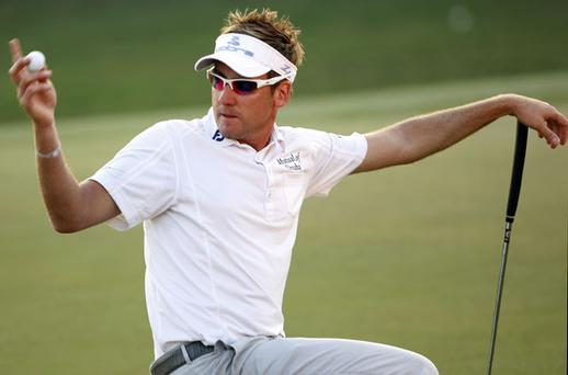 Ian Poulter, signals for a rules official after dropping his ball on his marker, incurruing a one stroke penalty during the sudden death play-off at the Dubai World Championship play-off. Photo: Reuters