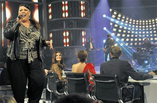 Mary Byrne performs behind the judges on Saturday's 'The X Factor' as Cheryl Cole looks on