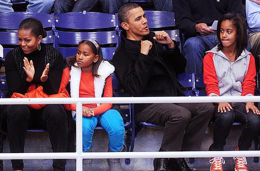 President Barack Obama with his wife First Lady Michelle Obama and daughters Malia and Sasha watch a college basketball game at Howard University