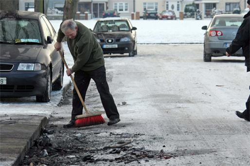 A resident on Hughes Road South, Crumlin, sweeps up debris after a burnt-out 4x4 vehicle used in a tiger raid was towed away